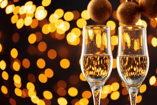 Two glasses of champagne and christmas baubles on shiny bokeh lights