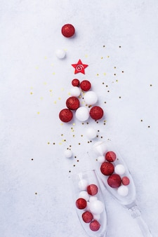 Two glasses for champagne and christmas champagne bottle with sprinkles in the form of christmas tree made of red and white toys balls decorated golden confetti on white.