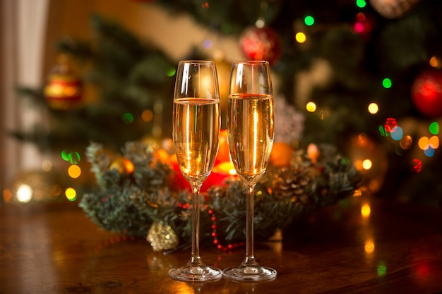 Two glasses of champagne and christmas wreath with candles on wooden table