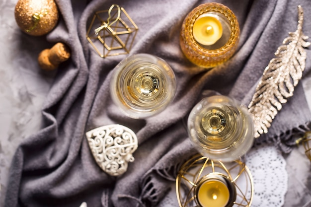 Two glasses of champagne on a gray plaid among gold