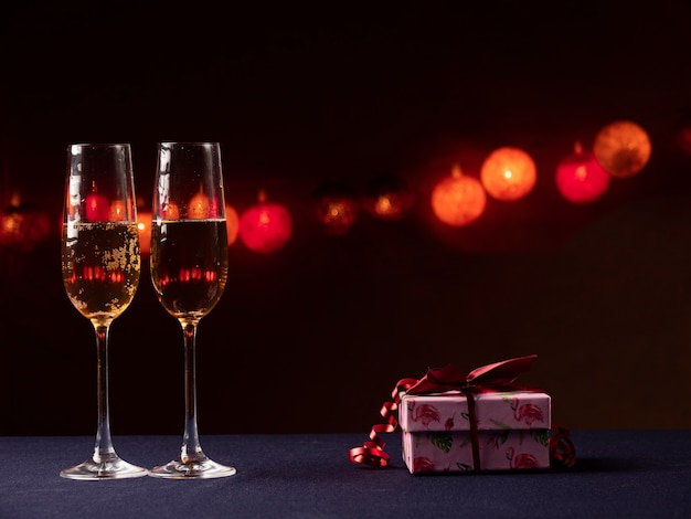 Two glasses of champagne, and a pink gift with a red ribbon on a black with light