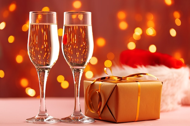 Two glasses of champagne and santa hat against bokeh lights