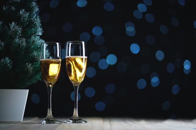 Two glasses of champagne and small christmas tree dark glow lights background. room for text