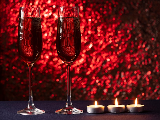 Two glasses of champagne stand with each other and next to them are three white burning candles on a pink