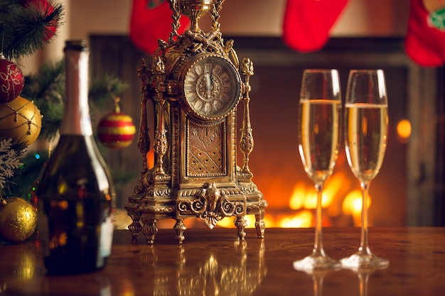 Two glasses of champagne on table next to old clock show 12 o'clock.