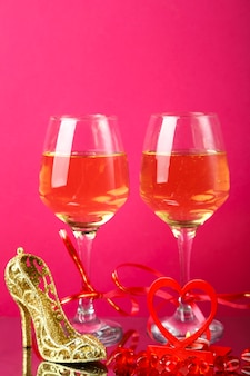 Two glasses of champagne tied with ribbons on a pink background next to a souvenir shoe and a candle in a candlestick. vertical photo