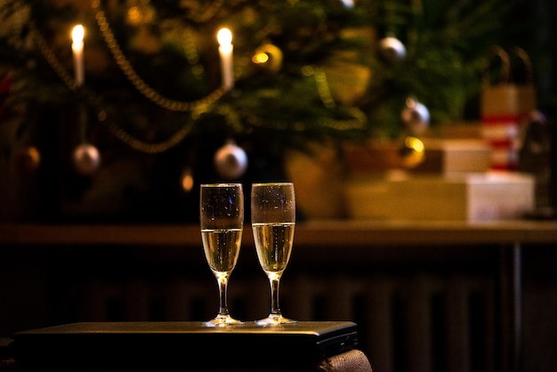 Two glasses of champagne toasting against christmas bokeh lights background