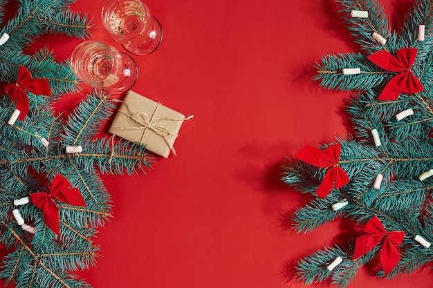 Two glasses of champagne with christmas tree branch and small gift on a red background. top view. copy space. still life. flat lay. inscription - happy new year 2018