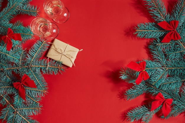 Two glasses of champagne with christmas tree branch and small gift on a red background