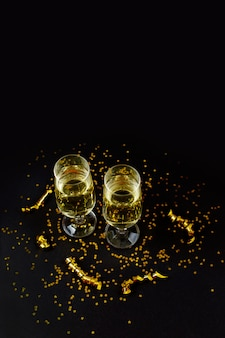 Two glasses of champagne with golden confetti, glitter