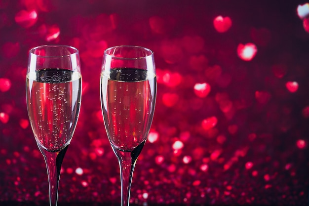 Two glasses of champagne with red heart shape bokeh on background. romantic dinner. happy valentine's day concept.