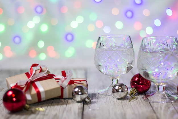 Two glasses of christmas champagne with gift boxes and balls decorations against light bokeh background.