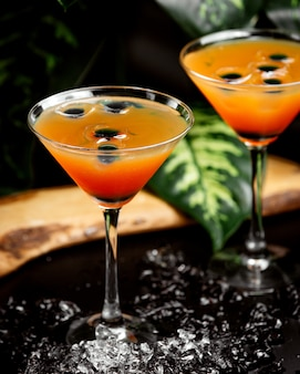 Two glasses of citrus cocktail in martini glasses garnished with olive ice cubes