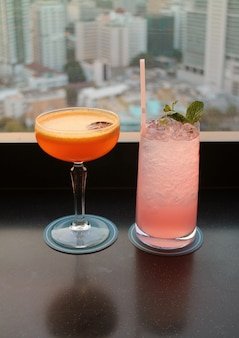 Two glasses of cocktail on the rooftop bar with blurry aerial urban view in background.