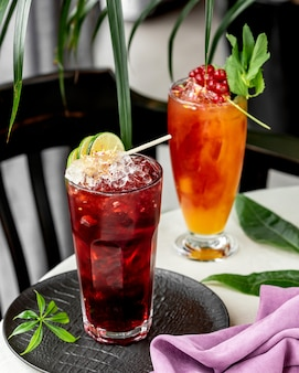 Two glasses of cocktails garnished with lime and redcurrant