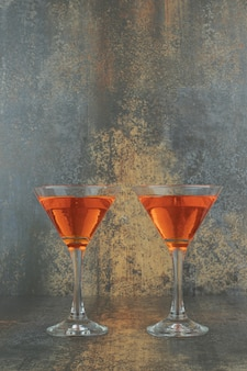 Two glasses of cocktails on marble table.