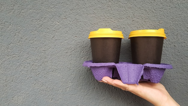 Two glasses of coffee in hand against the background of a blue wall. takeaway coffee in disposable black cups with yellow lids. morning coffee outside. copy space.