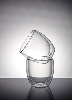 Two glasses for coffee or tea, standing on top of each other on a gray  with reflection