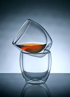 Two glasses for coffee or tea, standing on top of each other with tea in the upper glass with reflection