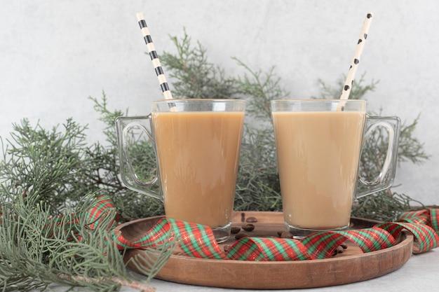 Due bicchieri di caffè con cannucce e nastro sul piatto di legno