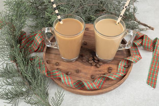 Due bicchieri di caffè con cannucce e nastro su piatto di legno