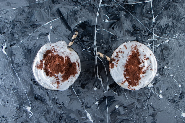Two glasses of coffee with whipped cream on marble surface.
