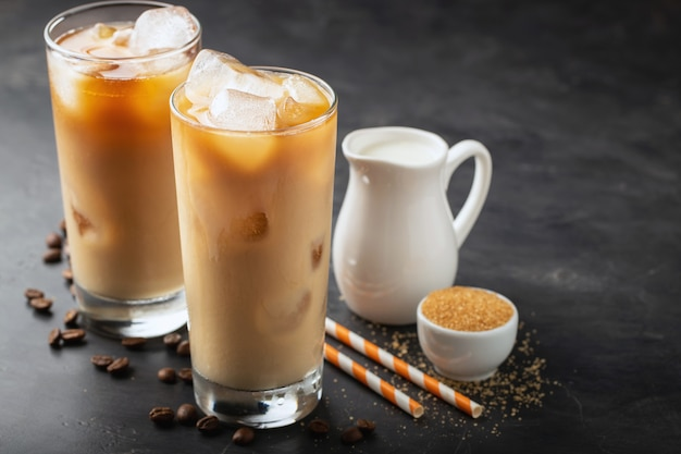 Two glasses of cold coffee on a dark background.