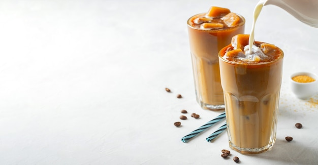 Two glasses of cold coffee on white background.