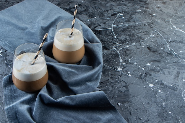 Two glasses of cold coffee with milk on marble surface.