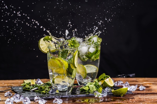 Two glasses of cool mojito on wooden table on black background