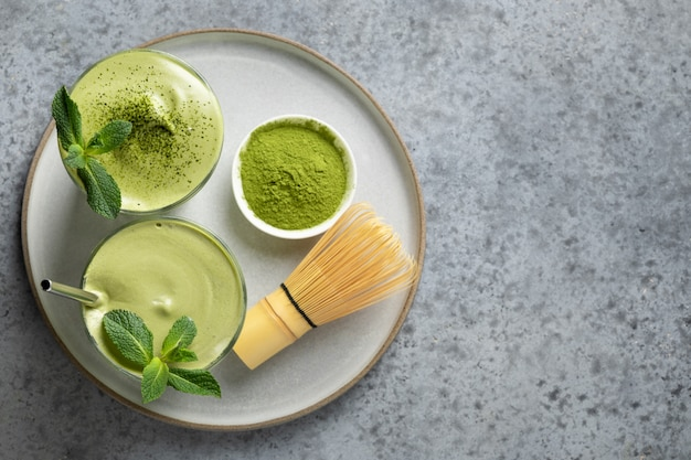 Two glasses of dalgona matcha latte tea, bamboo whisk and matcha powder on grey. view from above.