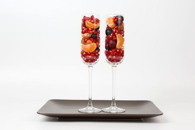 Два стакана с фруктами на светлом фоне