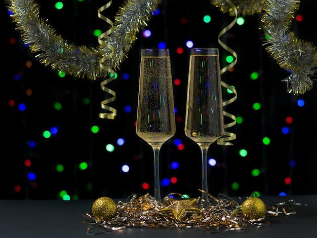 クリスマスの装飾が施されたスパークリングワインで満たされた2つのグラス。明けましておめでとうございます