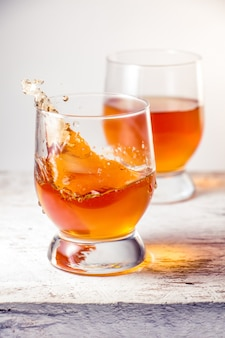 Two glasses filled with whiskey splash standing on the white wooden surface