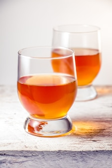 Two glasses filled with whiskey standing on the white wooden surface