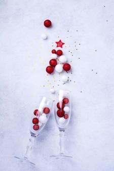 赤と白のおもちゃのボールで作られたクリスマスツリーの形で振りかけるシャンパンとクリスマスシャンパンボトルの2つのグラスは、白い背景に金色の紙吹雪を飾りました。上面図