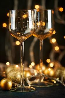 흐린 황금 빛에 대 한 와인과 황금 크리스마스 공 두 잔