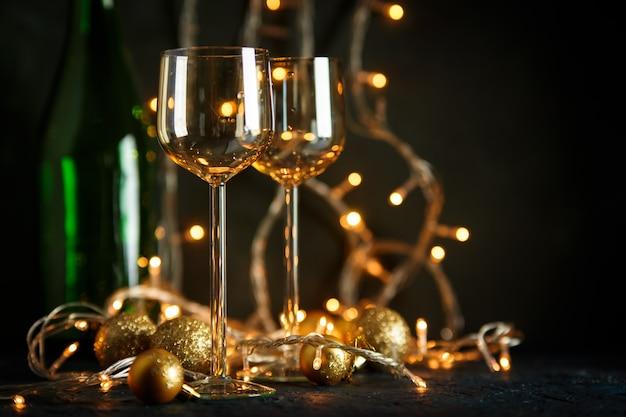 ぼやけた金色の光に対するワインと金色のクリスマスボール用のグラス2杯。