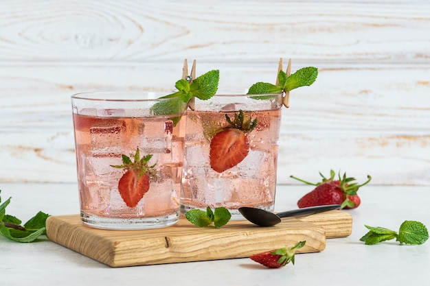 Two glasses of fresh iced strawberry mojito with mint on the serving board close up.
