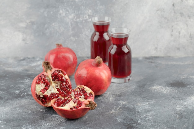 Two glasses of fresh juice with ripe pomegranate fruits on marble surface.