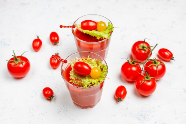 Two glasses of fresh tomato juice and tomatoes on gray concrete surface