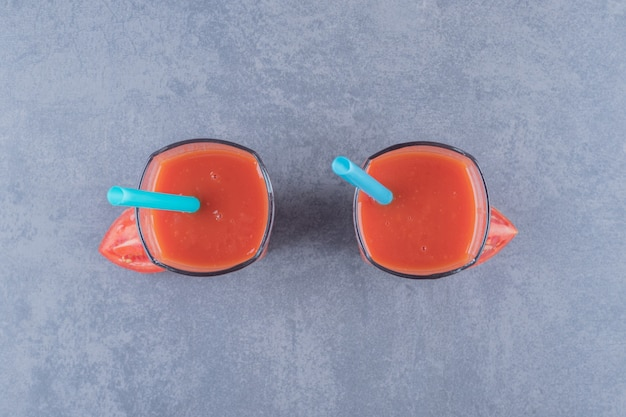 Two glasses of fresh tomato juice and tomatoes on a grey background.