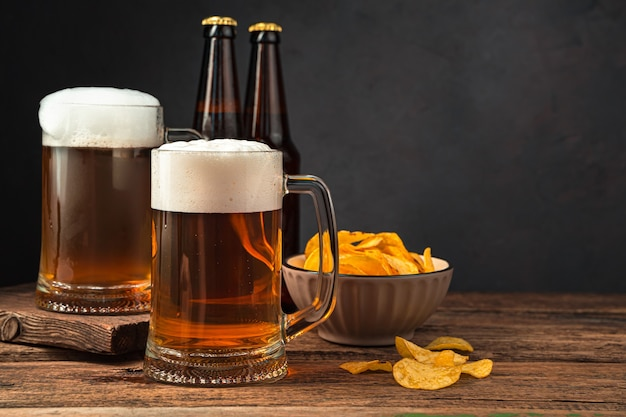 Two glasses of frothy beer chips and beer bottles on a brown background
