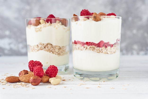 Two glasses of greek yogurt granola with raspberries, oatmeal flakes and nuts