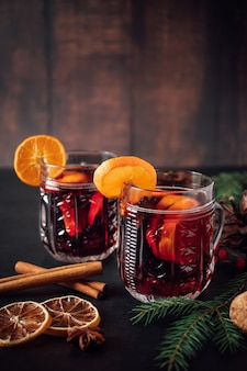 Two glasses of hot mulled wine with fruits and spices on a dark background. winter warming holiday drink.