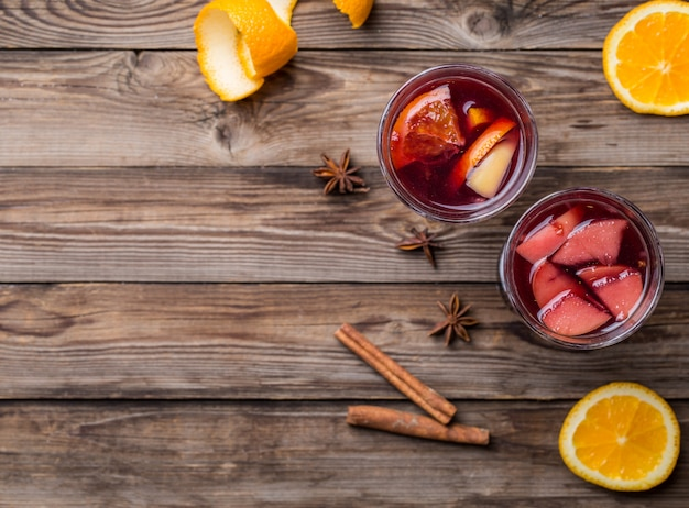 Two glasses of hot mulled wine with oranges, apples and spices