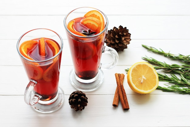 Two glasses of hot red mulled wine or gluhwein with orange, cinnamon sticks