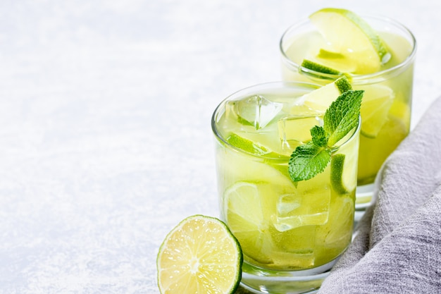 Two glasses of iced green matcha tea with lime, ice, fresh mint on light grey background.