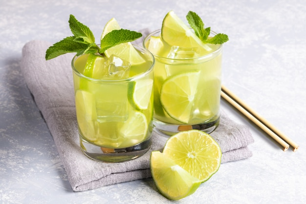 Two glasses of iced green matcha tea with lime, ice, mint, bamboo drinking straws on grey background.