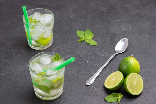 Two glasses of iced lemon drink. lime and spoon on table. black background. top view